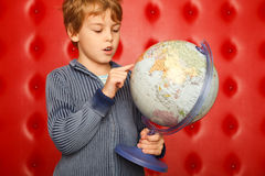 Boy pointing finger on globe. Portrait on red Royalty Free Stock Photos