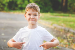 Boy pointing his fingers on a blank t-shirt, a place for your a stock photo