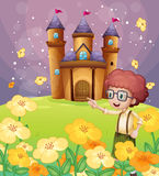 A boy pointing near the flowers in the hill with a castle Royalty Free Stock Photo