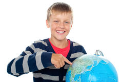 Boy pointing out a continent on the globe Royalty Free Stock Photography
