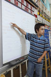 Boy Pointing On Projection Screen. School boy pointing on projection screen in the classroom Royalty Free Stock Image