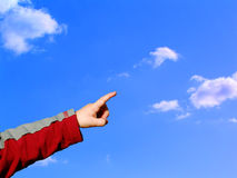 Boy pointing sky. Baby pointing sky with his left hand. Wears red and grey sweater. Saturated blue sky background with clouds Stock Photography
