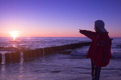 Boy pointing to sun. At sunset stock photography