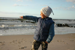 The boy is pointing on the water Royalty Free Stock Photos