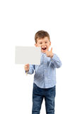 Boy pointing at white blank card. Portrait of happy laughing little boy pointing at white blank card isolated on white background Royalty Free Stock Image