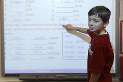 Boy Pointing On White Board stock photography