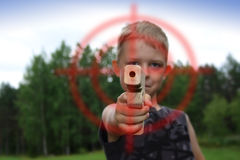 Boy pointing with wooden toy gun. Boy's toy gun pointing with crosshair symbol Royalty Free Stock Photo