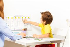 Boy points at activities on calendar learning days. Boy pointing at the calendar on the wall with days and activities arranged developing game with his parent royalty free stock photos