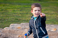 The boy points his finger. Four year old boy points his finger to the camera. He is  in the meadow. The boy stands near logs Stock Image