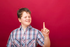 Boy points up on red background Stock Photography