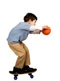 A boy poised to shoot a basketball. In it's hoop, isolated on white Stock Photo