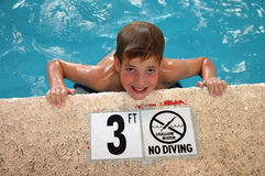 Boy in pool. Boy and  a Swimming pool depth marker with no diving warning Royalty Free Stock Photography
