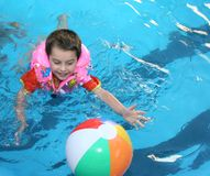 The boy in pool. The boy plays to water with a ball Royalty Free Stock Images