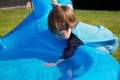 Boy in pool. A toddler playing in a small wading pool Stock Photography