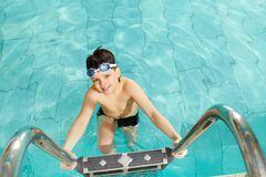 Boy in pool. Photo of happy lad in pool smiling at camera Stock Photo
