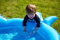 Boy in pool. A toddler playing in a small wading pool Royalty Free Stock Image