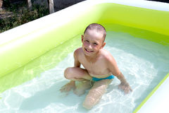 Boy in pool. Boy bathes in baby pool Royalty Free Stock Photo
