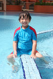 Boy at the pool. Boy wearing blue & red swim suit sitting at the pool Royalty Free Stock Photos