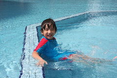 Boy at the pool. Boy wearing blue & red swim suit at the pool Royalty Free Stock Image