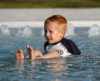 Boy in pool. A four year-old boy enjoys playing in a swimming pool on a warm, sunny day. Note: Wearing a swim-top can help protect against the harmful effects of Royalty Free Stock Photo