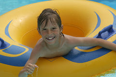 Boy in pool. Young boy floating in rubber ring in pool Stock Photos