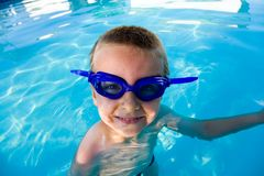 Boy in the pool. Young boy wearing diving mask or goggles in the swimming pool afternoon Royalty Free Stock Photography