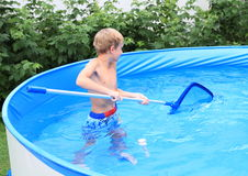 Boy in pool cleaning water. Little boy - freezing kid in wet blue shorts cleaning water in a swimming pool Royalty Free Stock Photo