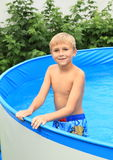 Boy in pool. Little boy - smiling kid in wet blue shorts in a pool Royalty Free Stock Image