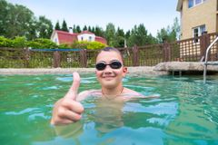 Boy in the pool outdoors stock images