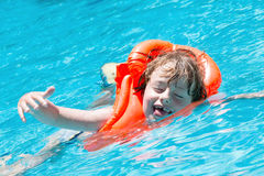 Boy in the pool. Portrait of a happy young boy with a red life jacket swimming in a pool Stock Photo