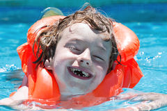 Boy in the pool. Portrait of a happy young boy with a red life jacket in a swimming pool Stock Photo