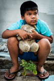 Boy poor with old teddy bear Royalty Free Stock Images