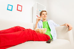 Boy with popcorn relaxing on white sofa at home Royalty Free Stock Photography