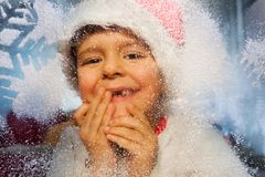 Boy portrait with New Year hat behind cold window. Close portrait of boy in santa hat looking though cold frosty winter window with snowflake Stock Images