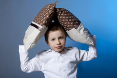 Boy portrait with pillows. Portrait of cute boy on blue background with brown pillows Royalty Free Stock Photos