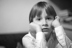 A boy. Portrait of a boy sitting at a table with a serious piercing gaze Royalty Free Stock Photos