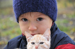Boy portrait in warm clothes hugging cat Royalty Free Stock Photos