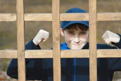 Boy poses behine a wooden latice. A young boy raises fits with a tight grin while posing for camera behind a wooden lattice stock images