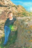 A boy poses for a photo shoot, leaning on a large rock on the rocks during a hike.  royalty free stock images