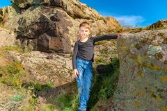A boy poses for a photo shoot, leaning on a large rock on the rocks during a hike.  stock photography