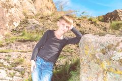 A boy poses for a photo shoot, leaning on a large rock on the rocks during a hike.  royalty free stock image