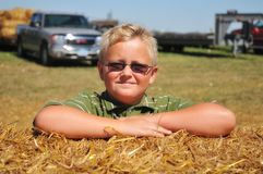 Boy Poses on Straw Bale. Boy in Glasses Poses on Straw Bale Stock Images