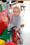 Boy Posing With Firefighter Ride-On. Cute Baby Boy Posing With Firefighter Ride-On Toy Car At Home, Close Up Portrait stock photo