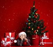 Boy posing in red hat near the Christmas tree stock photos
