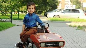 Boy posing sitting on a toy car stock footage