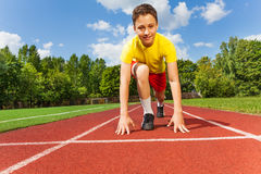 Boy in position to run with arms on the ground Stock Image