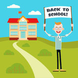 Boy with a poster go back to school. Smiling boy holds a poster with an inscription back to the school on the background of the road leading to the school Royalty Free Stock Image