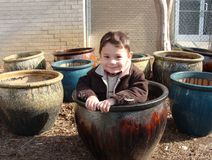 Boy in the pot. Little boy sitting in a pot among other flower pots Royalty Free Stock Photos