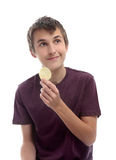 Boy with potato crisp looking sideways. A boy holding a single potato crisp chip and looking sideways at your message.  White background Stock Images