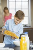 Boy pouring corn flakes in bowl with mother standing in background Stock Photo